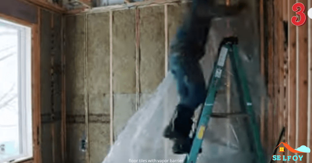 Man is on the ladder and installing vapor barrier