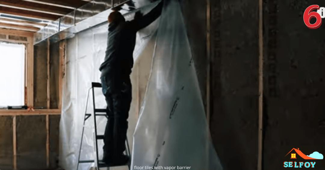 Man is installing polythene sheet vapor barrier over a big wall