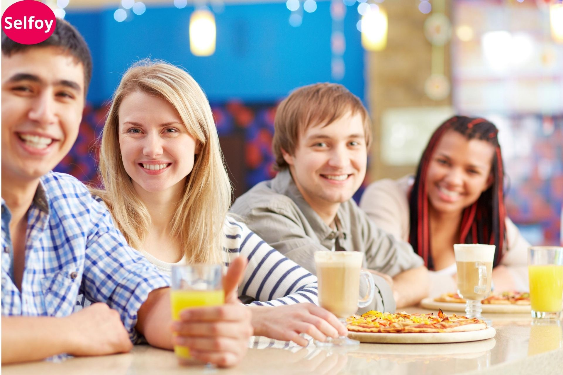 Good Personal Hygiene Helps to Develop Positive Self Esteem, two girls and two boys have a drink and pizza on their table and all are smiling