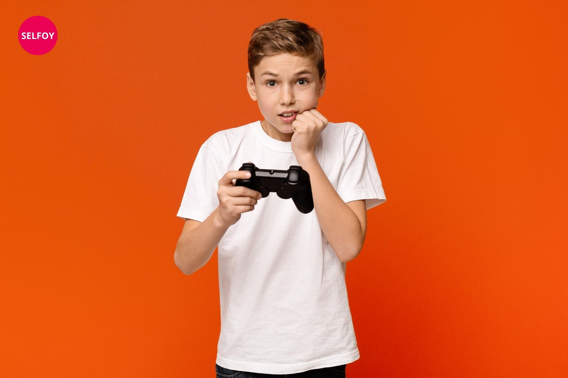 Boy has remote control of video game in hand and looks fearing and depicts low self esteem