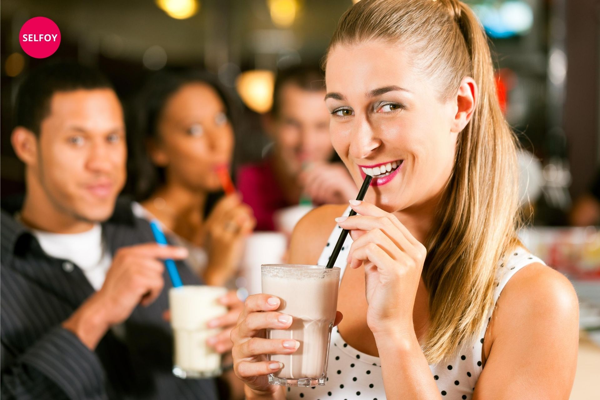 Girl is drinking shake and smiling and thats what are the characteristics of self confidence.