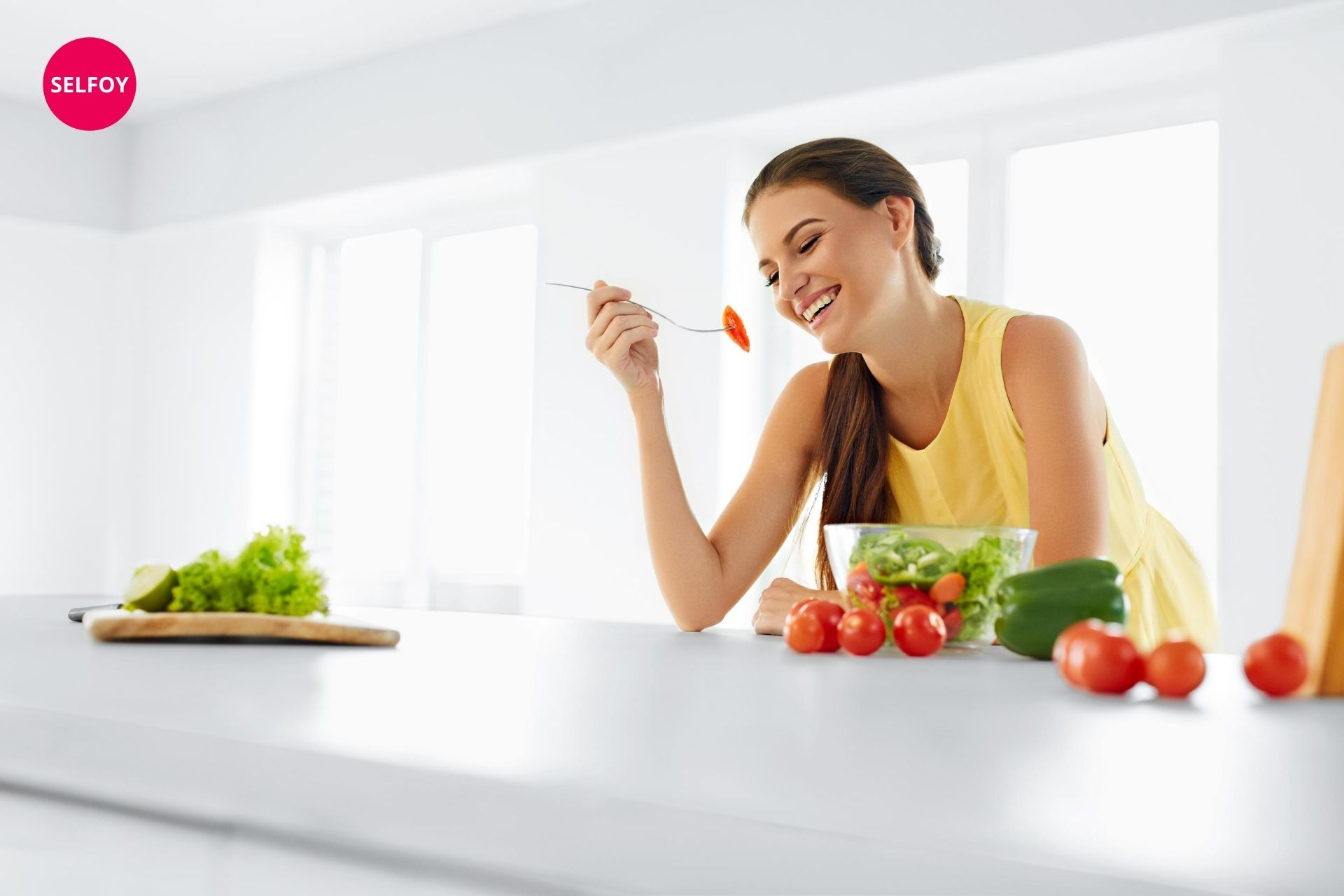 Woman wearing yellow top having spoon and eating salad