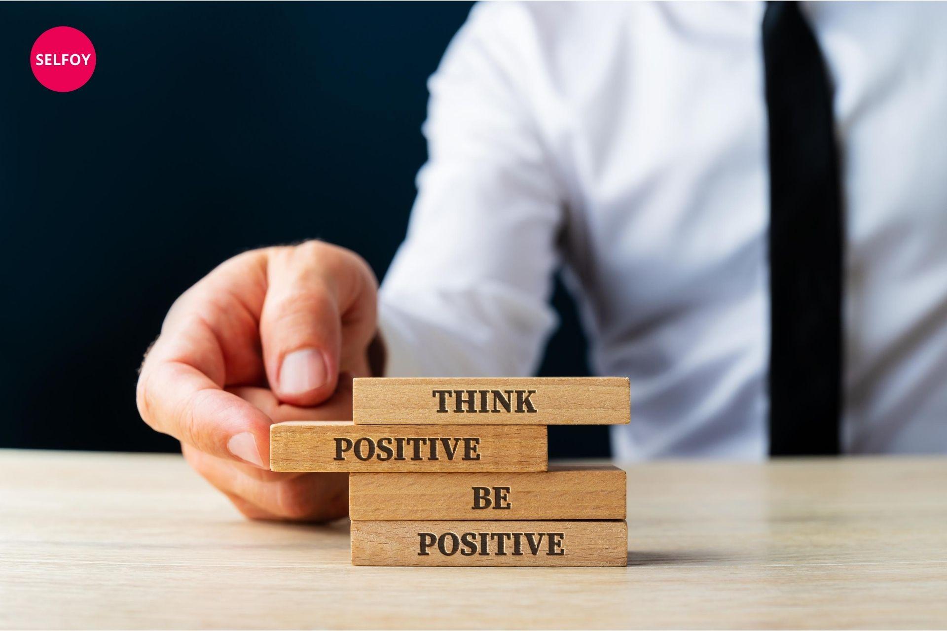Man's hand holding wooden art written think positive be positive