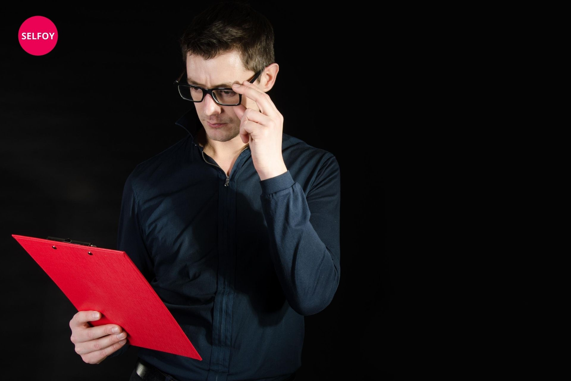 man wearing black shirt holding red file written about does autodidact work with self care to her team